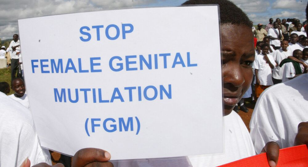 A woman in Kenya holds up a sign against FGM during a demonstration