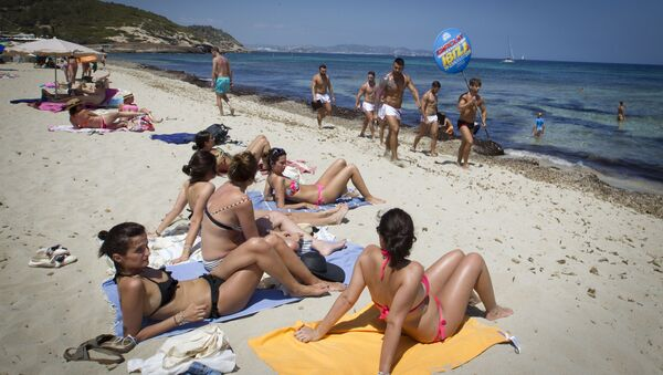 Girls sunbathing watch boys promoting a discotheque at Playa des Cavallet beach in Sant Josep de sa Talaia, on Ibiza Island on July 10, 2015.  - Sputnik International