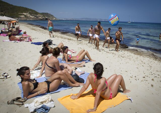 Girls sunbathing watch boys promoting a discotheque at Playa des Cavallet beach in Sant Josep de sa Talaia, on Ibiza Island on July 10, 2015.