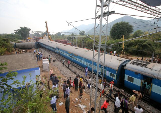 People stand near the derailed coaches of a passenger train near Kuneru village in Vizianagaram district, in the southern state of Andhra Pradesh, India, January 22, 2017