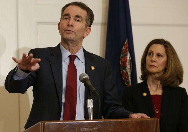 Virginia Gov. Ralph Northam, left, gestures as his wife, Pam, listens during a news conference in the Governors Mansion at the Capitol in Richmond, Va., Saturday, Feb. 2, 2019