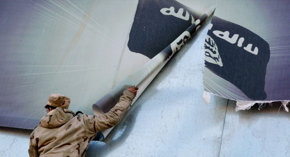 A member of the Iraqi security forces removes a banner bearing the logo of the Islamic State (IS) group in eastern Mosul on January 19, 2017