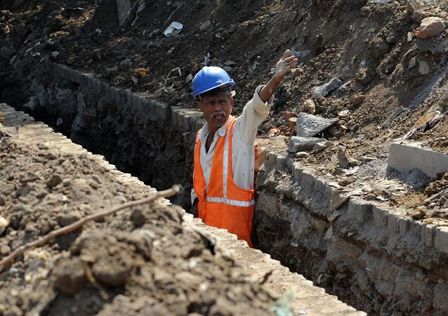 A labourer shouts instructions to co-workers standing inside a trench dug by the side of a busy throughfare to lay power cables in Mumbai on January 7, 2012