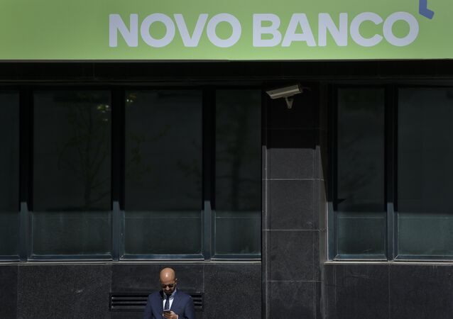 A man stands under a logo of Novo Banco Portuguese bank in Lisbon on March 31, 2017.