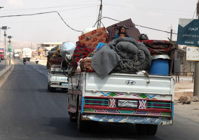 Syrians ride with their belongings in trucks as they head to safer areas in the town of Khan Sheikhun.