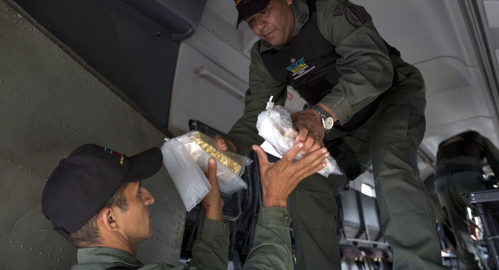 Members of a military agency that transports valuables remove gold bars from a military plane to be taken to Venezuela's Central Bank, at the Carlota military airport in Caracas, Venezuela, Thursday, March 1, 2018.