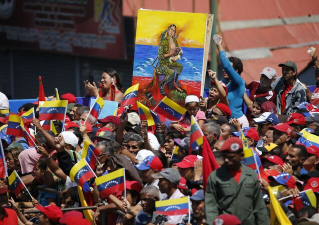 A woman holds a painting depicting a soldier breastfeeding during a pro-government rally in Caracas, Venezuela, Saturday, Feb. 2, 2019