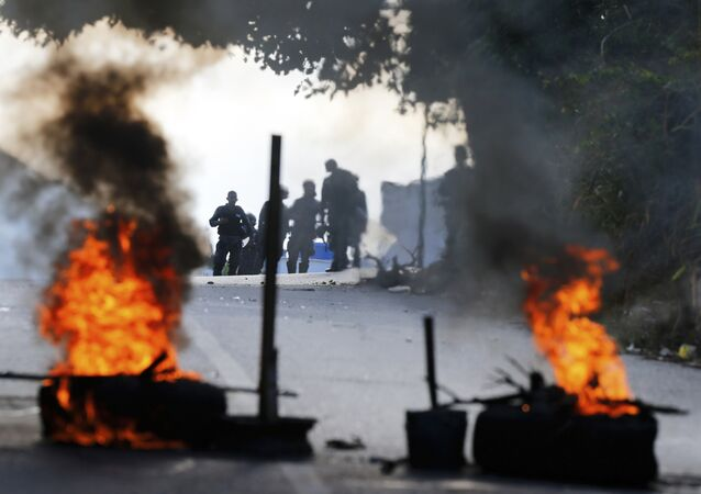 Bolivarian National Police stand behind a burning roadblock set up by anti-government protesters who are showing support for a mutiny by some National Guard soldiers in the Cotiza neighborhood of Caracas, Venezuela, Monday, Jan. 21, 2019