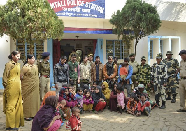 Indian police officials stand next to Rohingya Muslims after they were arrested in two northeastern states, outside a police station in Agartala, India, Tuesday, Jan. 22, 2019