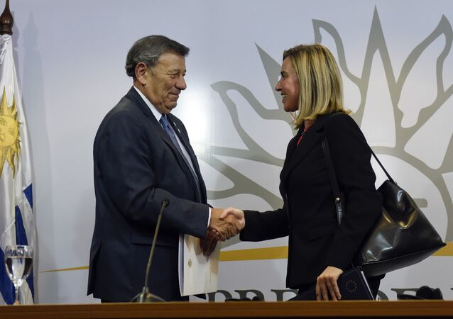 """Uruguay's Foreign Affairs Minister Rodolfo Nin, left, and European Union foreign policy chief Federica Mogherini shake hands at the end of an """"International Contact Group"""" meeting regarding the ongoing Venezuelan crisis, in Montevideo, Uruguay,Thursday, Feb. 7, 2019. Uruguayan President Tabare Vazquez is leading the meeting attended by leaders of 14 countries, including Spain, Italy, Portugal and Sweden."""