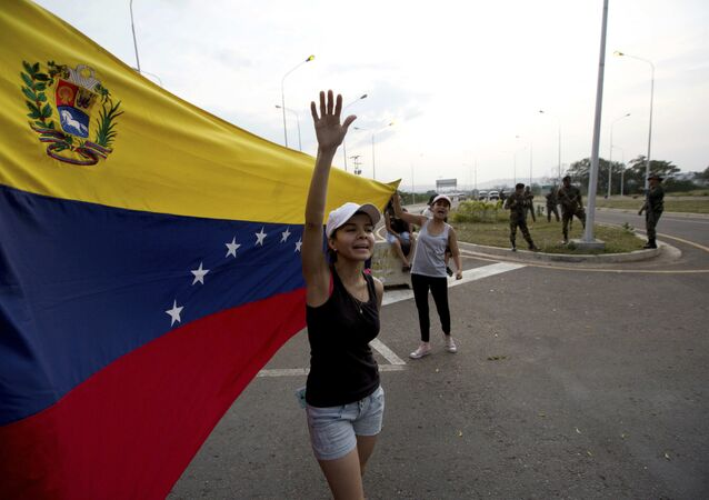 Woman shouts Welcome humanitarian aid as he waives Venezuelan flag in front aof a group of Venezuelan Army soldiers and National Guard officers blocking the main access to the Tienditas International Bridge that links Colombia and Venezuela, near Urena, Venezuela, Thursday, Feb. 7, 2019