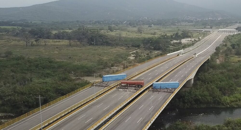 This image taken from video, shows a fuel tanker, cargo trailers and makeshift fencing, blocking the Tienditas International Bridge in an attempt to stop humanitarian aid entering from Colombia, as seen from the outskirts of Cucuta, on Colombia's border with Venezuela, Wednesday, Feb. 6, 2019. Immigration authorities say the Venezuelan National Guard built the roadblock a day earlier.