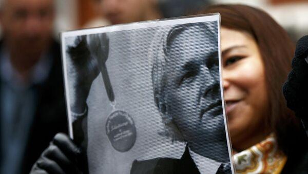 A supporter of Julian Assange holds a poster after prosecutor Ingrid Isgren from Sweden arrived at Ecuador's embassy to interview him in London - Sputnik International