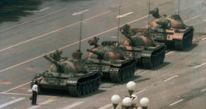 Tank Man blocks a column of Type 59 tanks heading east on Beijing's Chang'an Boulevard (Avenue of Eternal Peace) near Tiananmen Square during the Tiananmen Square protests of 1989. This photo was taken from the sixth floor of the Beijing Hotel, about half a mile away, through a 400 mm lens. The name and fate of the man is unknown