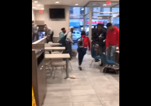 People scream and run as a prankster drops a white rat from a cage onto the floor of a crowded McDonald's in Newark, New Jersey