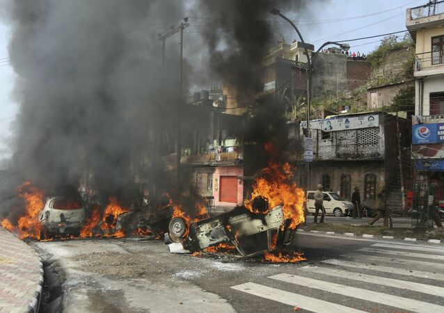Vehicles stand in flames after it was set on fire by a mob during a protest against Thursday's attack on a paramilitary convoy, in Jammu, India, Friday, Feb.15, 2019