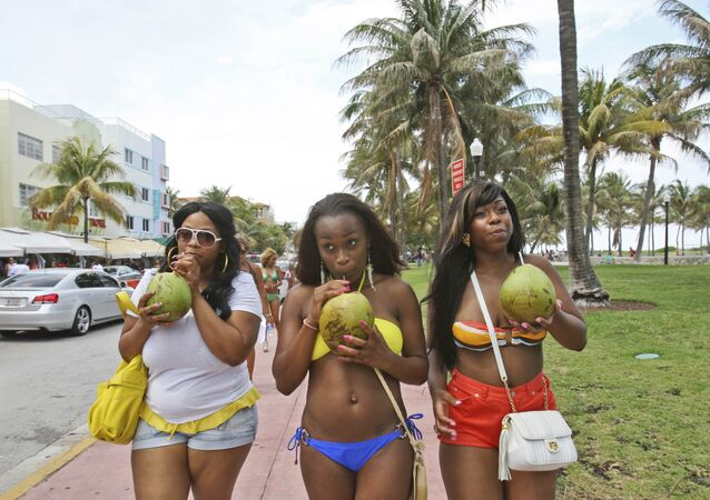 Tai Derrow, left, of Houston, Texas, Shaena Wilson, center, of Orlando, Fla., and Sprano Samuels, of Houston, Texas., drink coconut water as they walk down Ocean Drive while they enjoy their Memorial Day weekend in the South Beach section of Miami, Beach, Fla., Friday, May 28, 2010.