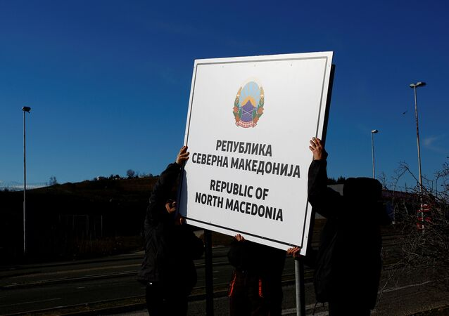 Workers set up a sign with Macedonia's new name at the border between Macedonia and Greece