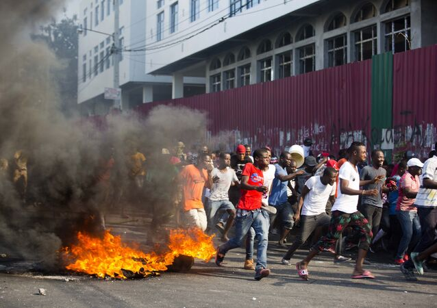 Demonstrators run away during a protest to demand the resignation of President Jovenel Moise and demanding to know how Petro Caribe funds have been used by the current and past administrations, in Port-au-Prince, Haiti, Saturday, Feb. 9, 2019. Much of the financial support to help Haiti rebuild after the 2010 earthquake comes from Venezuela's Petro Caribe fund, a 2005 pact that gives suppliers below-market financing for oil and is under the control of the central government.