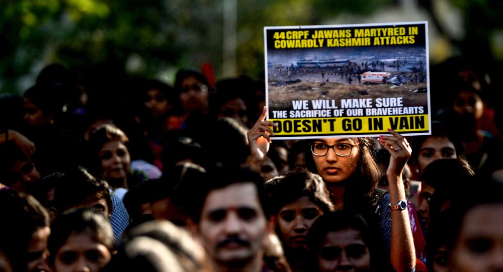 An Indian student holds a poster during a procession to pay tribute to the Central Reserve Police Force (CRPF) troopers in Chennai on February 16, 2019, following an attack on a CRPF convoy in Kashmir