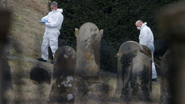 French gendarmes conduct their investigation as they examine graves that were desecrated with swastikas in the Jewish cemetery in Quatzenheim, near Strasbourg, France, February 19, 2019 - Sputnik International
