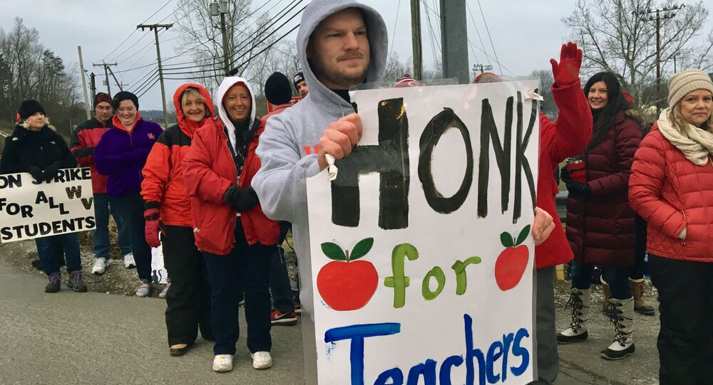 Striking teachers wave at passing cars outside Poca High School Tuesday, Feb. 19, 2019, in Poca, W.Va. Poca is in Putnam County, the only county in the state where public schools were held on the first day of the strike