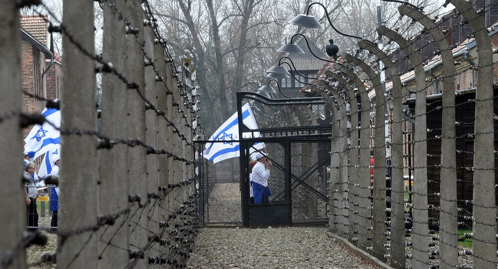 Participants with Israeli flags pass a barbed wire fence at the former Nazi German Auschwitz-Birkenau death camp during the 'March of the Living' at in Oswiecim, Poland on April 16, 2015