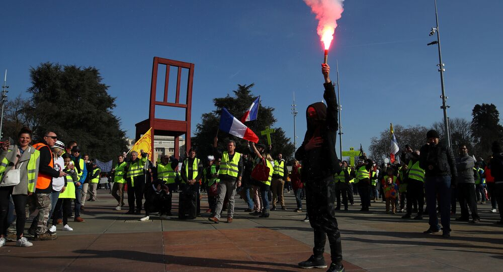 A person holds up a flare as people wearing yellow vests demonstrate outside the United Nations ahead of the Human Rights Council in Geneva, Switzerland, February 20, 2019
