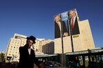 A man walks past a Likud election campaign billboard, depicting U.S. President Donald Trump shaking hands with Israeli Prime Minister Benjamin Netanyahu, in Jerusalem February 4, 2019