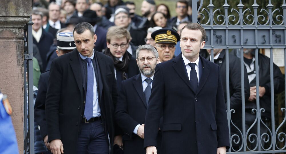 French President Emmanuel Macron, right, with France's Chief Rabbi Haim Korsia, center, leave the Jewish cemetery where tombs were tagged with swastikas in Quatzenheim, eastern France, Tuesday, Feb.19, 2019.