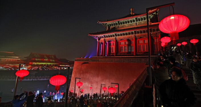 Visitors tour the Forbidden City decorated with red lanterns and illuminated with lights during the Lantern Festival in Beijing, Tuesday, Feb. 19, 2019.