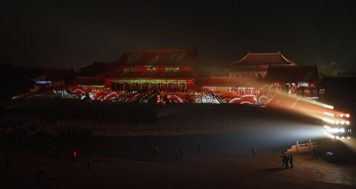 Visitors tour the Forbidden City projected with colorful lights during the Lantern Festival in Beijing, Tuesday, Feb. 19, 2019.