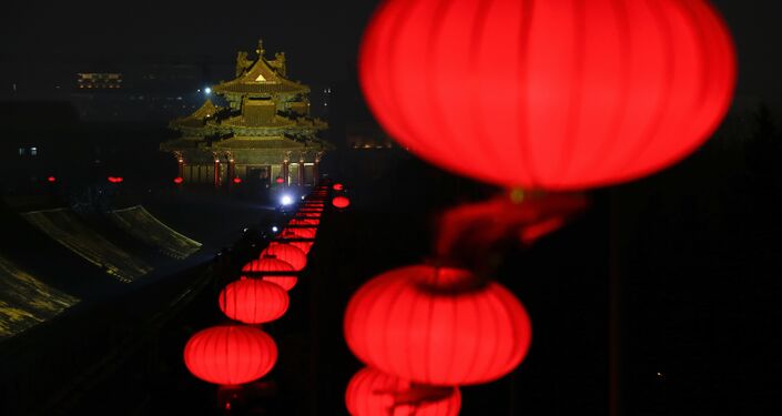 In this Tuesday, Feb. 19, 2019, photo, lanterns is decorated near a Turret of the Forbidden City projected with lights for the Lantern Festival in Beijing.