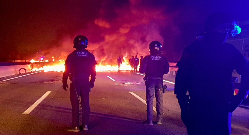 Police officers stand next to burning barricades settled to block the AP7 highway during a regional strike near Girona, Spain, February 21, 2019