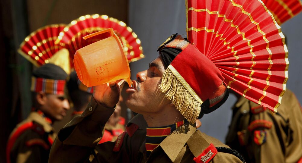 A new recruit of the Indian Border Security Force (BSF) drinks water before the start of a passing out parade ceremony in Humhama, on the outskirts of Srinagar, India, Tuesday, April, 26, 2011