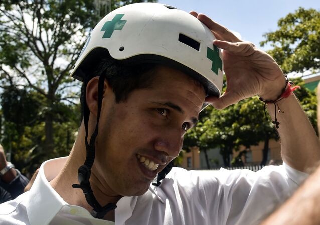 Venezuelan opposition leader and self declared acting president Juan Guaido wears a Green Cross helmet as he posses for a picture with volunteers of the movement Aid and Freedom Venezuela Coalition after delivering a speech in Caracas, on February 16, 2019