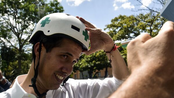 Venezuelan opposition leader and self declared acting president Juan Guaido wears a Green Cross helmet as he posses for a picture with volunteers of the movement Aid and Freedom Venezuela Coalition after delivering a speech in Caracas, on February 16, 2019 - Sputnik International
