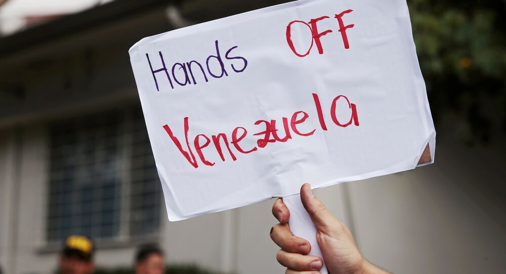 A supporter of Venezuela's President Nicolas Maduro holds a sign after Venezuelan opposition leader Juan Guaido's designated ambassador to Costa Rica Maria Faria took control of Venezuela's embassy, in San Jose, Costa Rica February 20, 2019.