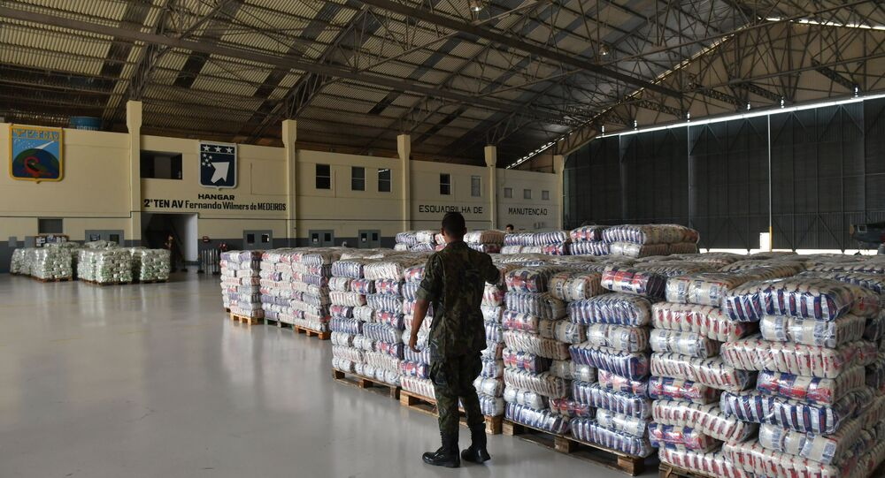 A Brazilian soldier walks near packages of rice and sugar that are part of the humanitarian aid for Venezuela, at Ala 7 air base in Boa Vista, Roraima state, Brazil in the border with Venezuela, on February 22, 2019.