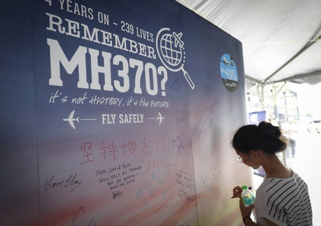 A girl writes a condolence message during the Day of Remembrance for MH370 event in Kuala Lumpur, Malaysia.