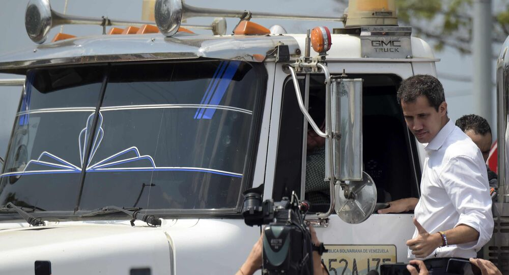 Venezuelan opposition leader Juan Guaido gives his thumb up from the side of a truck carrying humanitarian aid
