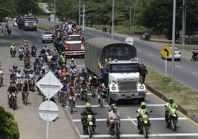 People ride atop and alongside semi-trailers accompanying U.S. humanitarian aid destined for Venezuela, in Cucuta, Colombia, Saturday, Feb. 23, 2019 .