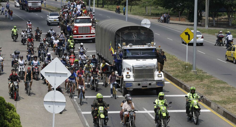People ride atop and alongside semi-trailers accompanying U.S. humanitarian aid destined for Venezuela, in Cucuta, Colombia, Saturday, Feb. 23, 2019 .