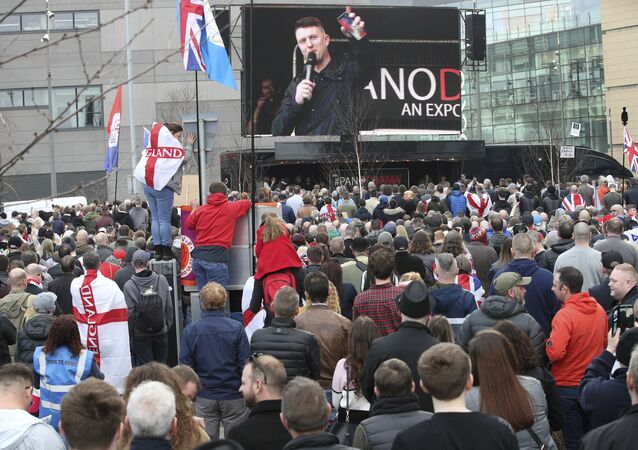Former leader and founder of the English Defence League, Tommy Robinson seen on screen, as he addresses an EDL protest over a TV program, outside the BBC building in Salford, England, Saturday Feb. 23, 2019.