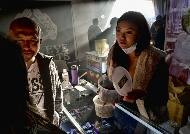 A vendor shows a customer marijuana Moon rocks, a combination of the weed strain dipped in hash oil and sprinkled with kief.at a farmers market style cannabis event Kushstock 6.5 in Adelanto Calif