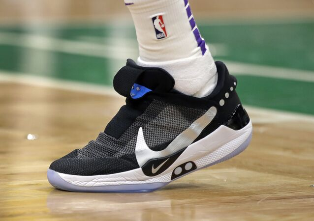 In this Feb. 7, 2019, photo, Los Angeles Lakers forward Kyle Kuzma walks on the court during an NBA basketball game against the Boston Celtics in Boston. He is wearing Nike's latest performance basketball shoes, which from concept to reality, took about three years to put together. Or 30 years, depending on how you count. The Nike Adapt BB _ a self-lacing smart shoe that can be controlled by a smartphone _ gets released to the public on Sunday, Feb. 17, 2019, a date that just happens to coincide with the NBA All-Star Game in Charlotte. It has a motor embedded within the shoe, and a hefty $350 price tag. It has a motor embedded within the shoe, and a hefty $350 price tag