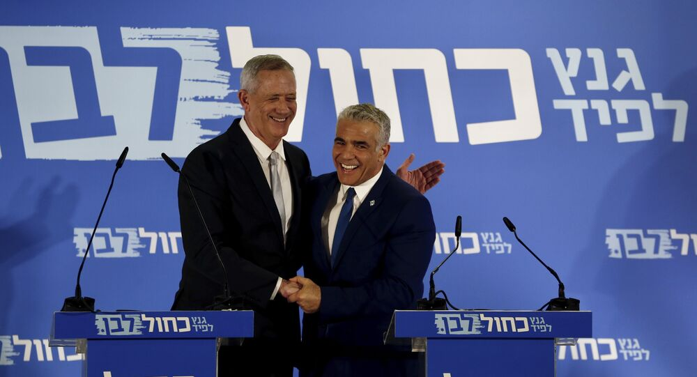 Retired Israeli military chief Benny Gantz, left, smiles with Yair Lapid, head of the Yesh Atid party as they launch joint list for the upcoming Israeli elections in Tel Aviv, Israel, Thursday, Feb. 21, 2019