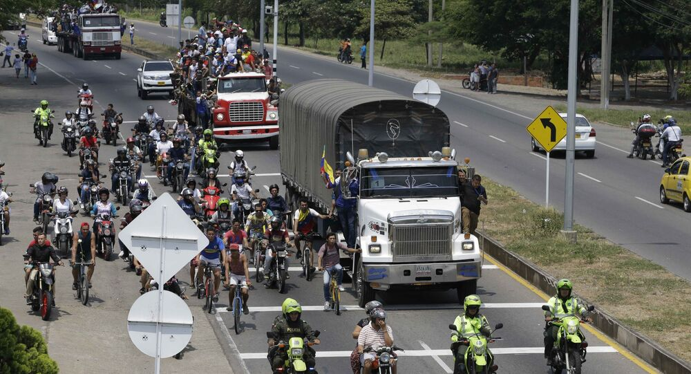 Venezuelans ride atop and alongside semi-trailers accompanying U.S. humanitarian aid destined for Venezuela, in Cucuta, Colombia, Saturday, Feb. 23, 2019