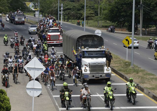 Venezuelans ride atop and alongside semi-trailers accompanying U.S. humanitarian aid destined for Venezuela, in Cucuta, Colombia, Saturday, Feb. 23, 2019