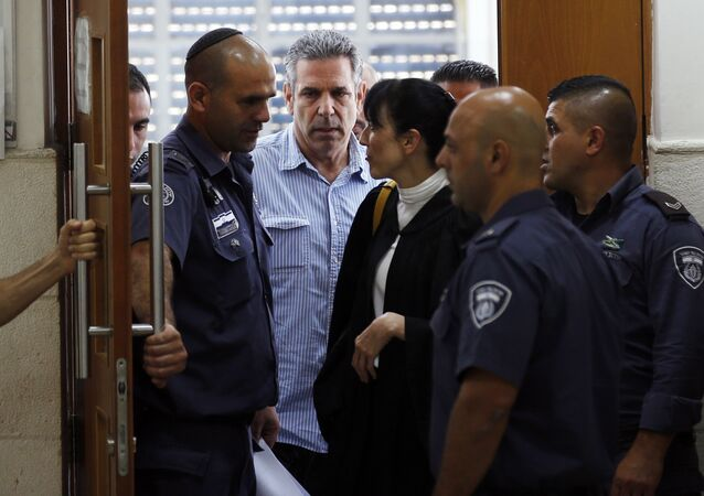 Gonen Segev, center, a former Israeli government minister indicted on suspicion of spying for Iran, is escorted by prison guards as he leaves the court in Jerusalem, Thursday, July 5, 2018